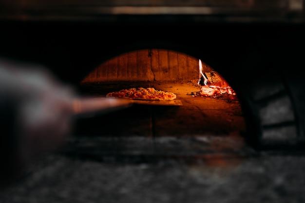 Pizza assando em forno de lenha.