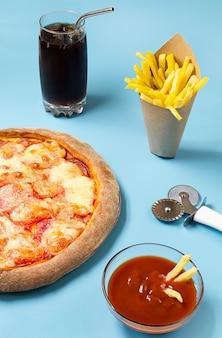 Pizza, batata frita e refrigerante com gelo em um fundo azul