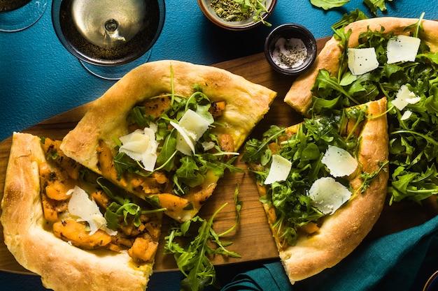 Pizza branca italiana tradicional com queijo taleggio e pecorino, abóbora caramelizada e rúcula na mesa azul