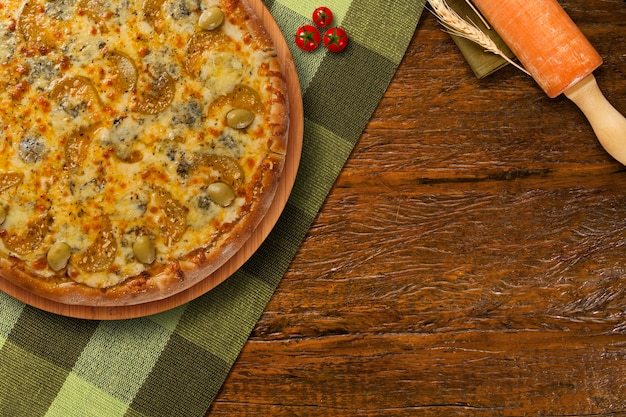 Pizza brasileira caseira quente em mesa de madeira