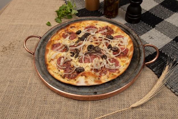 Pizza brasileira com calabresa, queijo, cebola e azeitona preta, vista de cima