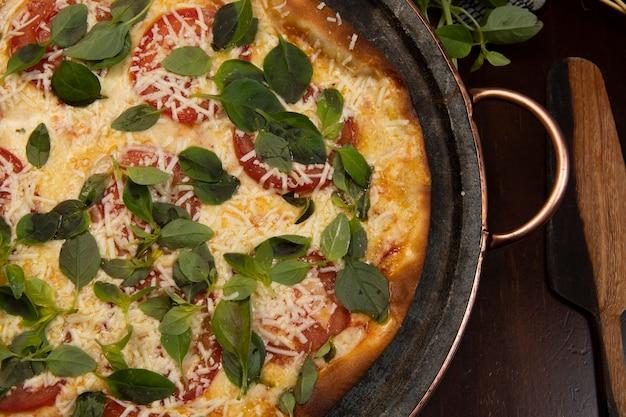 Pizza brasileira com calabresa, queijo e rúcula, vista de cima