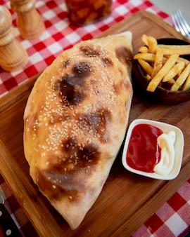 Pizza calzone com batatas fritas e ketchup