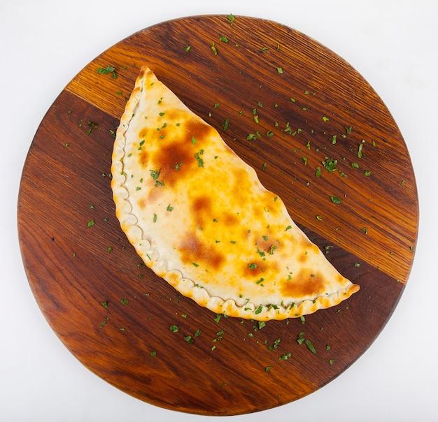 Pizza calzone com molho vermelho e branco em uma placa de madeira