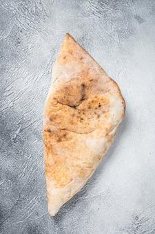 Pizza calzone italiana com frango e queijo. fundo branco. vista do topo.