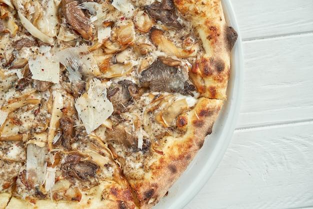 Pizza caseira apetitosa com cogumelos diferentes, parmesão e molho branco em um prato branco sobre um branco