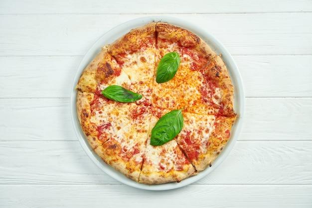 Pizza caseira apetitosa com margarita com tomate, manjericão e mussarela em um prato branco sobre um branco