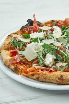 Pizza caseira apetitosa com queijo jamon, parmesão, rúcula e straccella em um prato branco sobre um branco