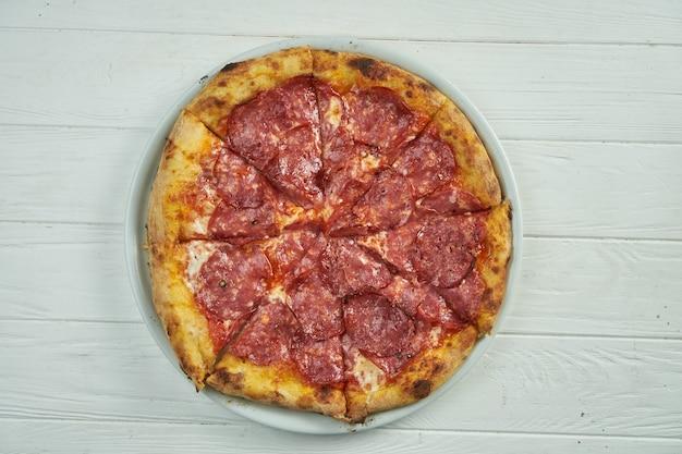 Pizza caseira apetitosa com salame, queijo derretido e molho vermelho em um prato branco sobre um branco