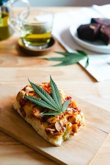 Pizza caseira com folha de maconha ou cannabis na bandeja de madeira.