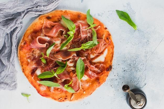Pizza caseira com jamon, mussarela e manjericão folhas sobre fundo antigo concreto. vista do topo.