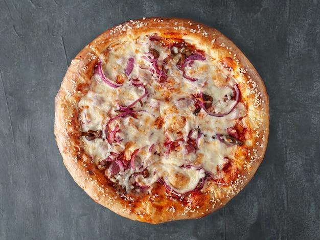 Pizza caseira com linguiça de caça, cebolas roxas em conserva, cogumelos, queijo mussarela e molho de tomate. lado largo. vista de cima. sobre um fundo cinza de concreto. isolado.