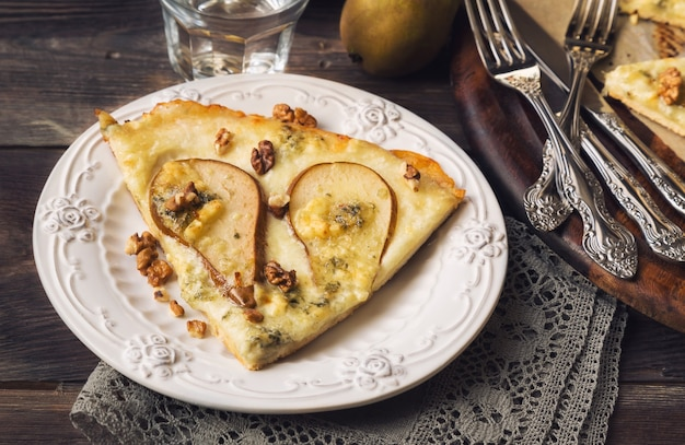 Pizza caseira com pêra, queijo azul, mussarela e nozes em superfície de madeira rústica.