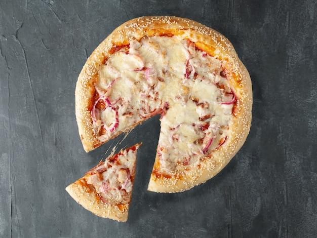 Pizza caseira com presunto e fatias de bacon, mussarela e queijos parmesão cebolas vermelhas em conserva