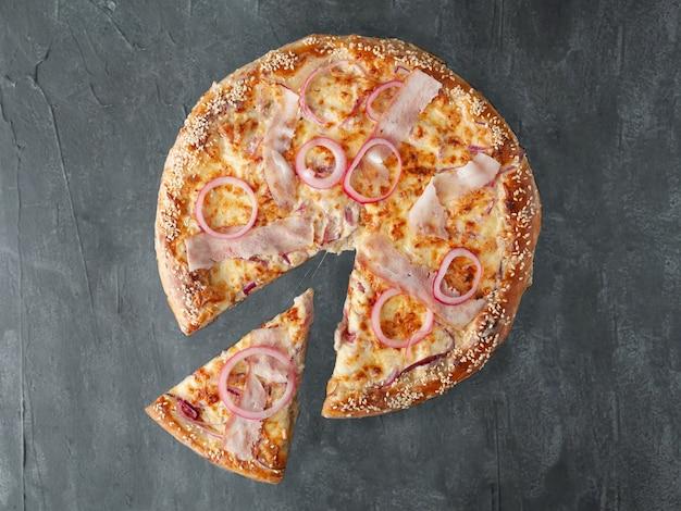 Pizza caseira com rodelas de bacon, cebola roxa em conserva, queijo mussarela, queijo parmesão e molho de tomate. um pedaço é cortado da pizza. vista de cima. sobre um fundo cinza de concreto. isolado.