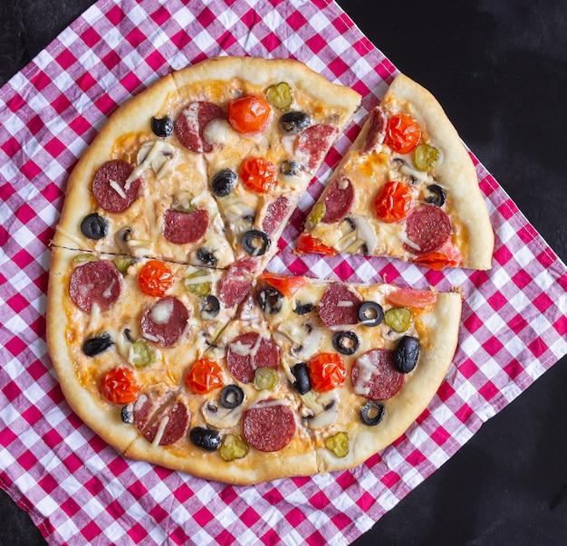 Pizza caseira com salame, cogumelos e tomate cereja em um fundo preto. uma toalha xadrez vermelha. vista do topo.