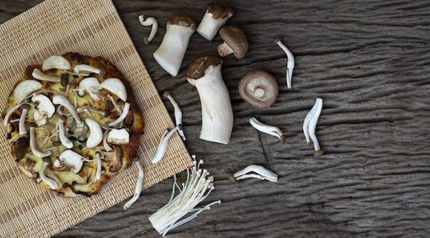 Pizza caseira de cogumelos no fundo de uma mesa de madeira