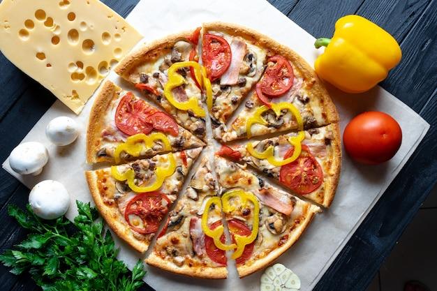 Pizza caseira deliciosa com ingridients na vista superior da parede escura. flat lay pizza fatiada com presunto, tomate e queijo derretido. vista de cima da cozinha italiana tradicional. comida para o almoço