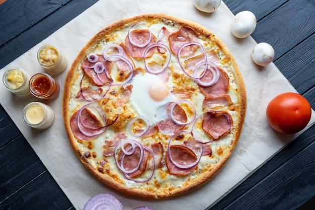 Pizza caseira deliciosa com ingridients na vista superior do fundo escuro. pizza plana leiga com salame, ovo, cebola e queijo derretido. viw de cima da cozinha italiana tradicional. comida para o almoço