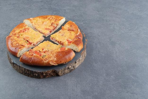 Pizza caseira fatiada na peça de madeira.