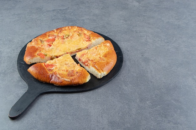 Pizza caseira fatiada na tábua de cortar preto.