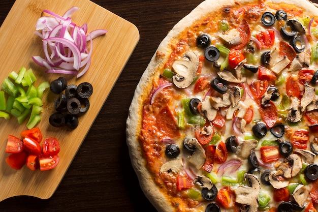 Pizza caseira fresca, vista de cima, na mesa de madeira escura.