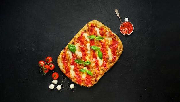 Pizza caseira margarita quadrada ou pinza com mussarela derretida, manjericão verde fresco e molho de tomate na vista superior, preta