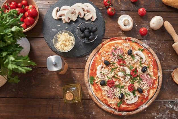 Pizza caseira na placa de madeira, com tomate e salame, cogumelos, estilo italiano na mesa de madeira velha, vista superior