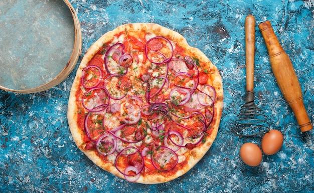 Pizza caseira, ovos, corola em azul rústico. vista do topo