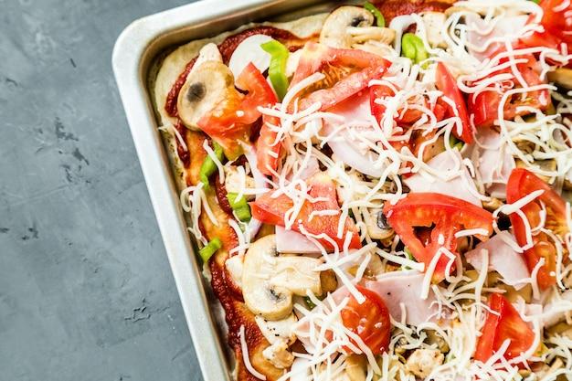 Pizza caseira saborosa com cogumelos, tomates, galinha, queijo no concreto cinzento.