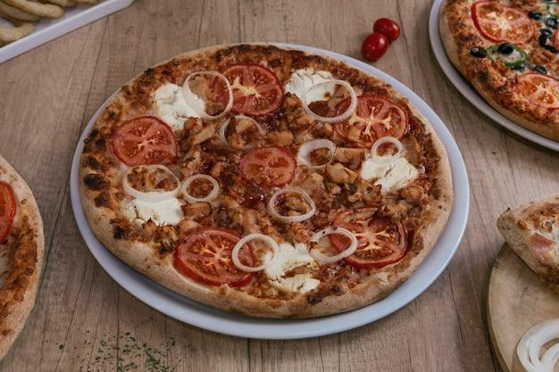 Pizza cheia de kebab, presunto e queijo azul