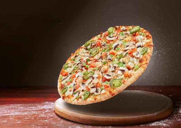 Pizza clássica em uma superfície de mesa de madeira escura e uma dispersão de farinha. conceito de menu de restaurante de pizza