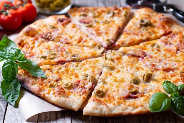 Pizza com azeitonas, tomate, presunto. natureza morta. pizza variada