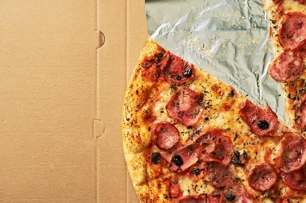 Pizza com bacon em uma caixa de papelão. fechar-se. vista do topo. entrega de pizza. menu de pizza.