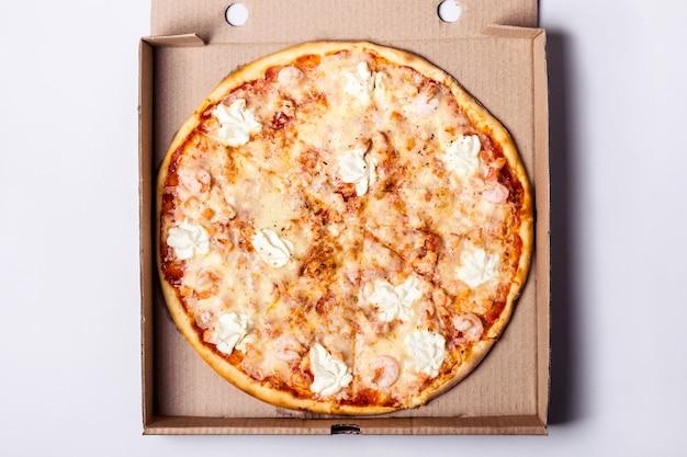 Pizza com camarão de frutos do mar e salmão em caixa de embalagem em fundo cinza.