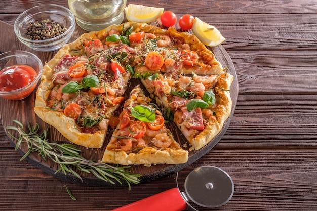 Pizza com camarão, queijo, manjericão e tomate em uma superfície de madeira