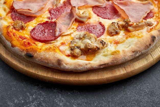 Pizza com carne, salsicha, carne e cogumelos em um fundo cinza com lugar para texto. pizza 4 carnes