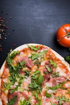 Pizza com cobertura de folhas de bacon e rúcula perto de tomate suculento e pimenta preta na superfície preta texturizada