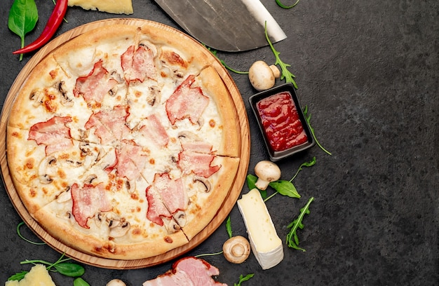 Pizza com cogumelos bacon e queijo em um fundo de pedra com espaço de cópia para o seu texto