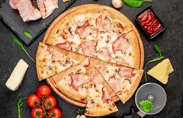 Pizza com cogumelos bacon e queijo em um fundo de pedra
