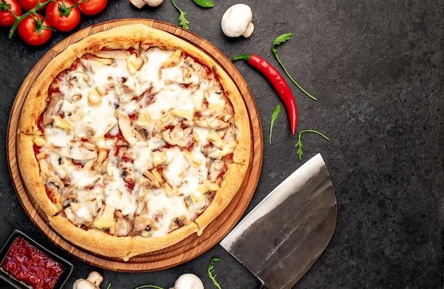 Pizza com cogumelos de frango e abacaxi em um fundo de pedra com espaço de cópia para o seu texto
