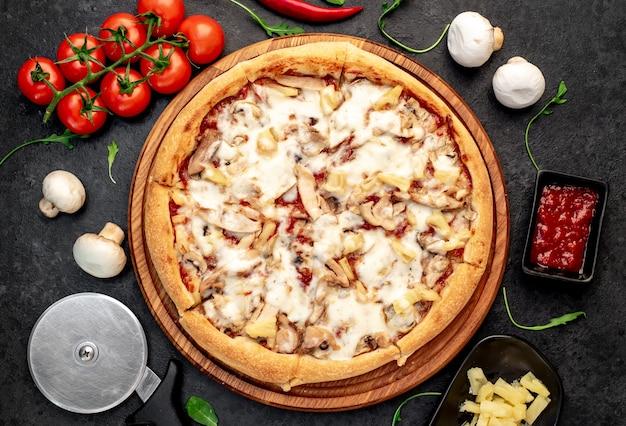 Pizza com cogumelos de frango e abacaxi em um fundo de pedra