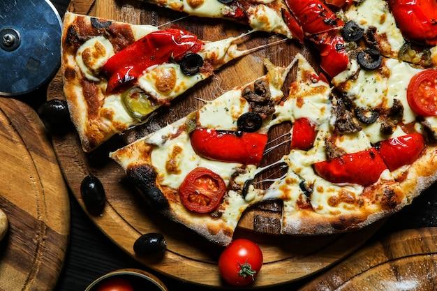 Pizza com enchidos, tomate, queijo, azeitonas e pimenta