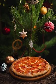 Pizza com enfeites de natal na mesa de madeira