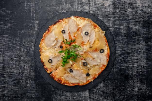 Pizza com frango, abacaxi, queijo e azeitonas na pedra e um fundo preto de madeira riscado
