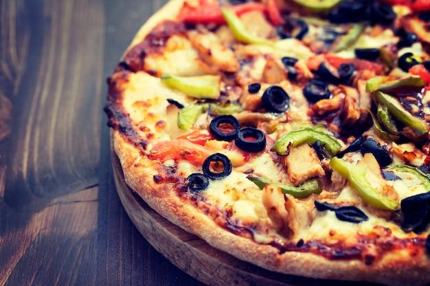 Pizza com frango e azeitonas na superfície de madeira marrom