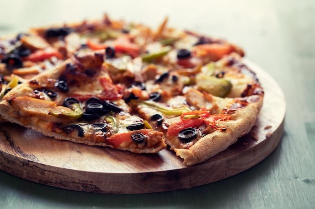 Pizza com frango e azeitonas na superfície de madeira verde