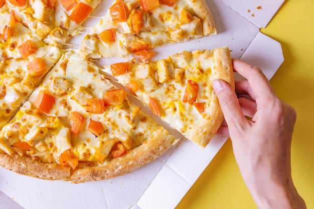 Pizza com frango e tomate em uma caixa. mão tira uma fatia de pizza.