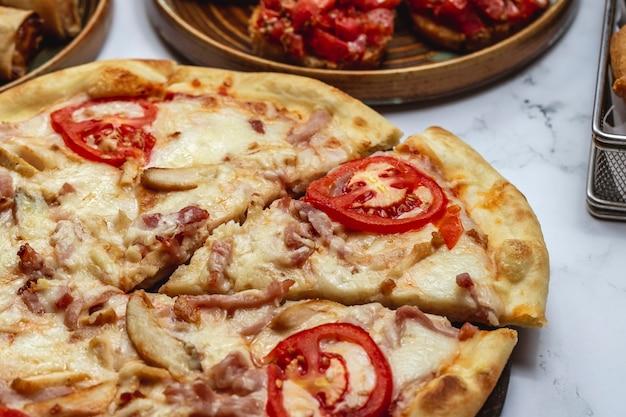 Pizza com frango tomate queijo cogumelos vista lateral