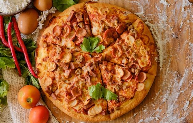 Pizza com fundo de madeira, vista superior. pizza com carne picada, aipo e queijo mussarela de perto.